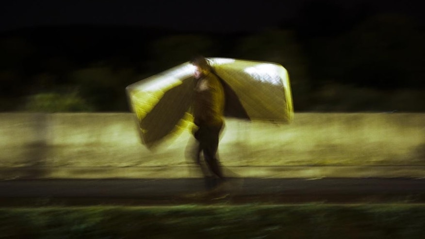 In this photo taken with a long shutter speed, a refugee carries a mattress at a makeshift camp while waiting to cross the border from Croatia into Slovenia near the border station of Obretzje in Slovenia Sunday, Sept. 20, 2015. (AP Photo/Markus Schreiber)