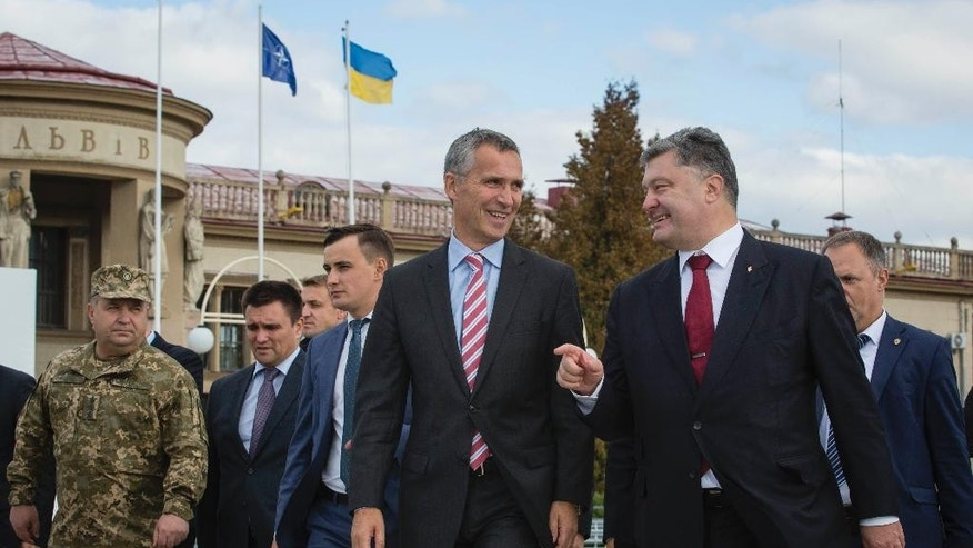 Ukrainian President Petro Poroshenko, right, and NATO Secretary General Jens Stoltenberg talk to each other at the a city airport in Lviv, western Ukraine, Monday, Sept. 21, 2015. Stoltenberg arrived in Ukraine for a joint exercise by NATO and Ukraine. (AP Photo/Mikhail Palinchak, Pool)