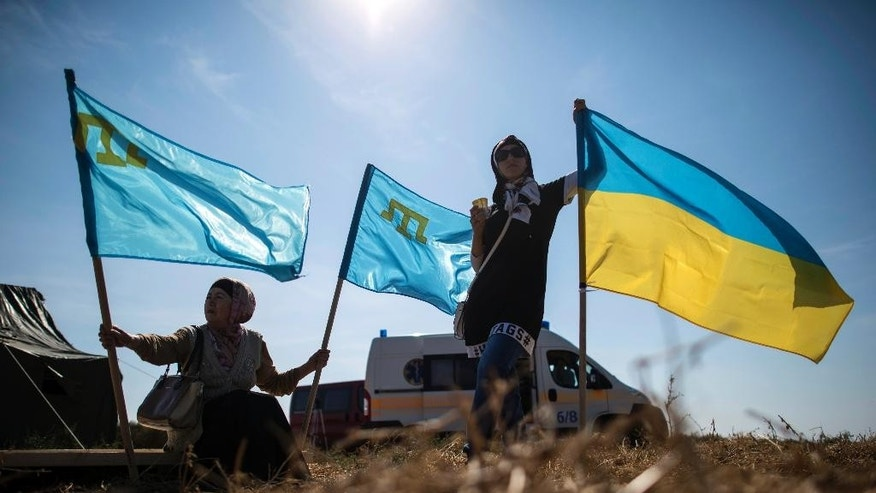 Local residents hold Ukrainian and Crimean Tatars flags in the village of Chongar, Ukraine, on Sunday, Sept. 20, 2015. The radical Right Sector group and Pro-Kiev Crimean tartars leadership organized improvised checkpoints on all three roads connecting the Ukrainian mainland and Russian-annexed Crimean peninsula, aiming to prevent trucks carrying goods to cross Russia-Ukraine border. (AP Photo/Evgeniy Maloletka)