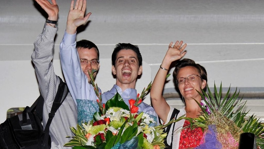 FILE - In this Sept. 24, 2011 file photo, Shane Bauer, from left, Josh Fattal and Sarah Shourd, Bauer's fiance, wave before leaving for the United States after Oman helped mediate their release, at the airport in Muscat, Oman. Oman's announcement on Sunday, Sept. 20, 2015, that it negotiated the release of foreign hostages held by Yemen's Shiite Houthi rebels is the most recent example of the unassuming sultanate wielding its influence as one of the Middle East's most useful mediators of thorny disputes. (AP Photo/Sultan al-Hasani, File)