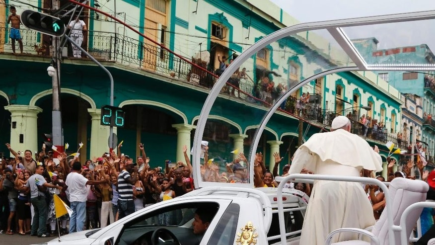 Pope Francis waves from his popemobile as he is transported to the San Cristobal Cathedral, in Havana, Cuba, Sunday, Sept. 20, 2015. Francis was finishing the day with a vespers service in Havana's cathedral, and a meeting with a group of Cuban youth. (AP Photo/Desmond Boylan)