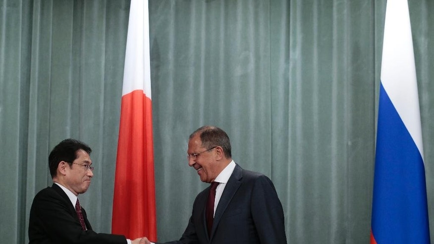 Russian Foreign Minister Sergey Lavrov, right, and his Japan's counterpart Fumio Kishida shake hands after their talks in Moscow, Russia, on Monday, Sept. 21, 2015. (AP Photo/Ivan Sekretarev)
