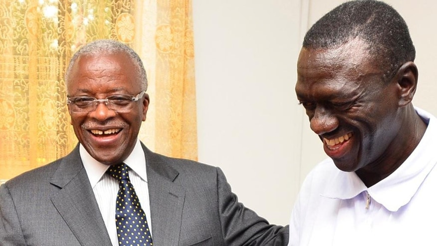 In this photo taken Friday, Sept. 11, 2015, former Prime Minister, Amama Mbabazi , left, chats with Forum for Democratic Change, Kizza Besigye,   in Naguru, Uganda.  The leaders of Uganda's main opposition parties are meeting Monday Sept. 21, 2015  in talks aimed at fronting a joint candidate to challenge the country's long-serving leader in elections next year. (AP Photo)