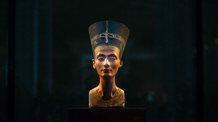 FILE - In this Sept. 10, 2014 file photo, a 3,300-year-old bust of Queen Nefertiti stands on its socle, at the New Museum in Berlin, Germany. An Egyptian official says the Antiquities Ministry gave an initial approval for the use of non-invasive radar to verify a theory that Queen Nefertiti's crypt may be hidden behind King Tutankhamun's 3,300-year-old tomb in the famous Valley of the Kings.  (AP Photo/Markus Schreiber, File)