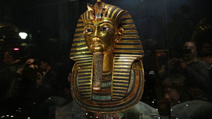 FILE - In this Saturday, Jan. 24, 2015, file photo, the gold mask of King Tutankhamun is seen in its glass case during a press tour, in the Egyptian Museum near Tahrir Square, Cairo, Egypt. An Egyptian official says the Antiquities Ministry gave an initial approval for the use of non-invasive radar to verify a theory that Queen Nefertiti's crypt may be hidden behind King Tutankhamun's 3,300-year-old tomb in the famous Valley of the Kings.  (AP Photo/Hassan Ammar, File)