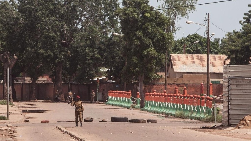 Burkina Faso troops, rear, provide security at a military check point in Ouagadougou, Burkina Faso, Tuesday, Sept. 22, 2015. Burkina Faso's coup leader said Tuesday that negotiations are still ongoing even though a deadline given by the military for the junta to disarm has expired. (AP Photo/Theo Renaut)