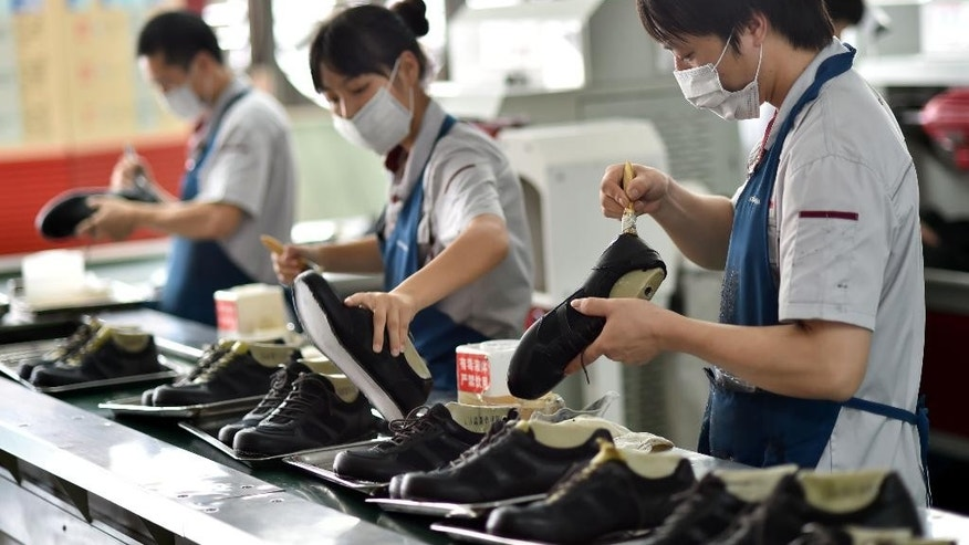 In this July 29, 2015 photo, workers assemble shoes in a shoe factory in Yongjia county in eastern China's Zhejiang province. The Caixin preliminary survey of factory purchasing managers released Wednesday, Sept. 23, 2015, showed that Chinese manufacturing activity fell to its lowest level in over 6 years, in the latest sign of the deepening slowdown in the world's second biggest economy. (Chinatopix Via AP) CHINA OUT