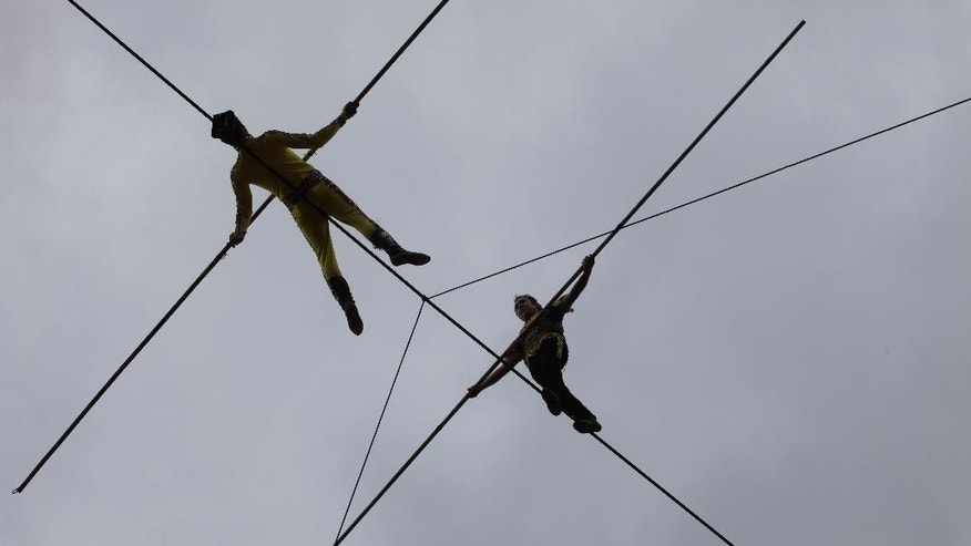 In this June 26, 2015 photo, Askar Obulqasim, right, and his partner Anwar perform walking on a tightrope during a show at a theme park outside Kunming in southwest China's Yunnan province. Already the holder of several tightrope world records, including the fastest walk across a 100-meter (330-foot) rope in 2013, Askar hopes to draw international attention to the profession known among fellow ethnic Muslim Uighurs as dawaz. (AP Photo/Helene Franchineau)
