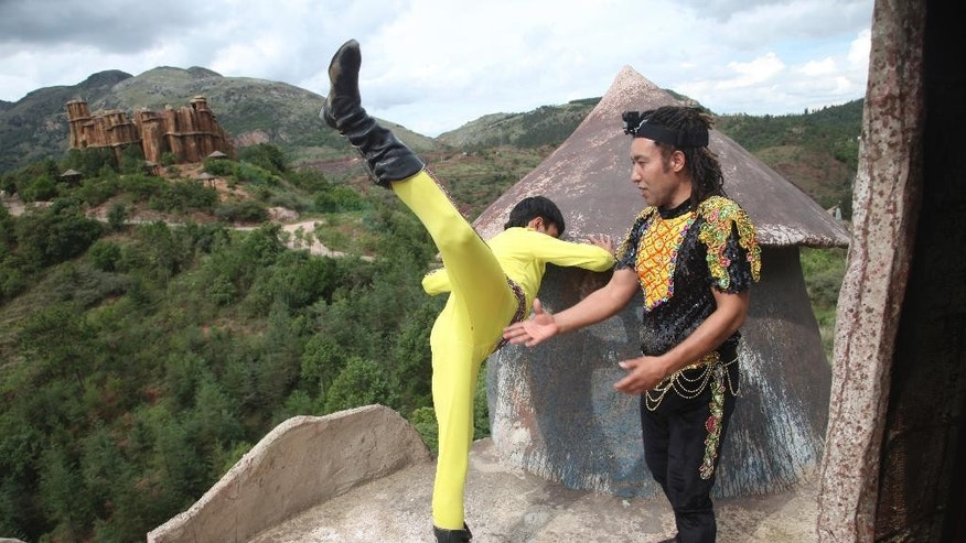 In this June 26, 2015 photo, Askar Obulqasim, right, and his partner Anwar warm up before performing on a tightrope at a theme park outside Kunming in southwest China's Yunnan province. Already the holder of several tightrope world records, including the fastest walk across a 100-meter (330-foot) rope in 2013, Askar hopes to draw international attention to the profession known among fellow ethnic Muslim Uighurs as dawaz. (AP Photo/Helene Franchineau)