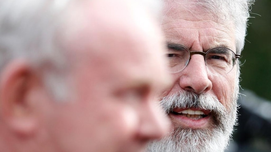 Sinn Fein party leader Gerry Adams, right, speaks to the media during a press conference at Stormont, Belfast, Northern Ireland, Monday, Sept. 21, 2015. The five main political parties met Monday with party-talks being aimed at resolving the current crisis threatening the power sharing institutions. (AP Photo/Peter Morrison)