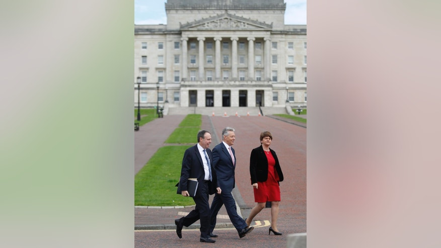 Democratic Unionist Party leader and Northern First Minister Peter Robinson, centre, walks with party members Nigel Dodds, left, and Arlene Foster, right as they arrive to hold a press conference at Stormont, Belfast, Northern Ireland, Monday, Sept. 21, 2015. The five main political parties met Monday with party-talks being aimed at resolving the current crisis threatening the power sharing institutions. (AP Photo/Peter Morrison)
