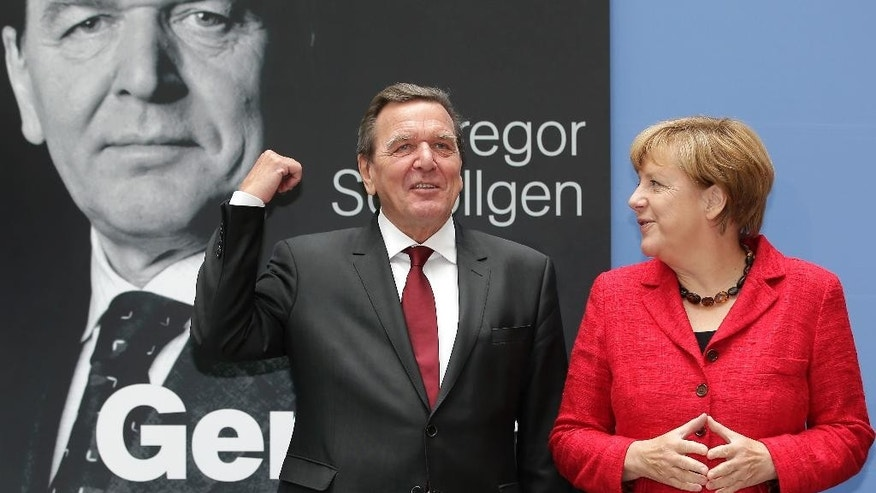 German Chancellor Angela Merkel, right, and former German Chancellor Gerhard Schroeder, left, pose during a photo call for the book presentation of Schroeder's biography in Berlin, Germany, Tuesday, Sept. 22, 2015. (AP Photo/Michael Sohn)