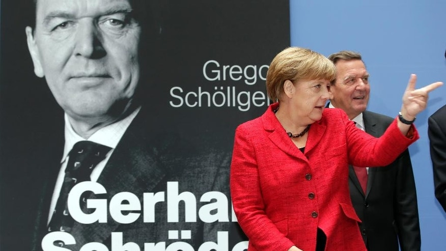 German Chancellor Angela Merkel, left, points as she and former German Chancellor Gerhard Schroeder, right, pose during a photo call for the book presentation of Schroeder's biography in Berlin, Germany, Tuesday, Sept. 22, 2015. (AP Photo/Michael Sohn)