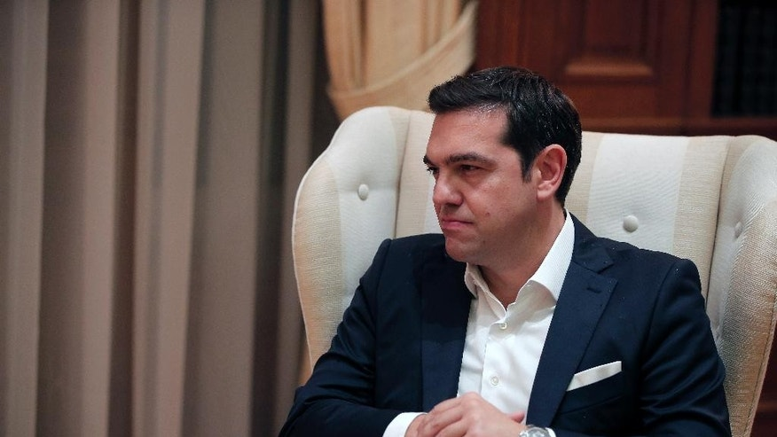The newly re-elected Prime Minister Alexis Tsipras listens to Greece's caretaker Prime Minister Vassiliki Thanou during a hand out ceremony at Maximos Mansion in Athens, Monday, Sept. 21, 2015. Syriza's victory Sunday marks a personal triumph for Tsipras, who served as prime minister between January and August — a tumultuous period that saw Greece's future in the 19-country eurozone come under real threat and strict banking controls imposed. (AP Photo/Lefteris Pitarakis)