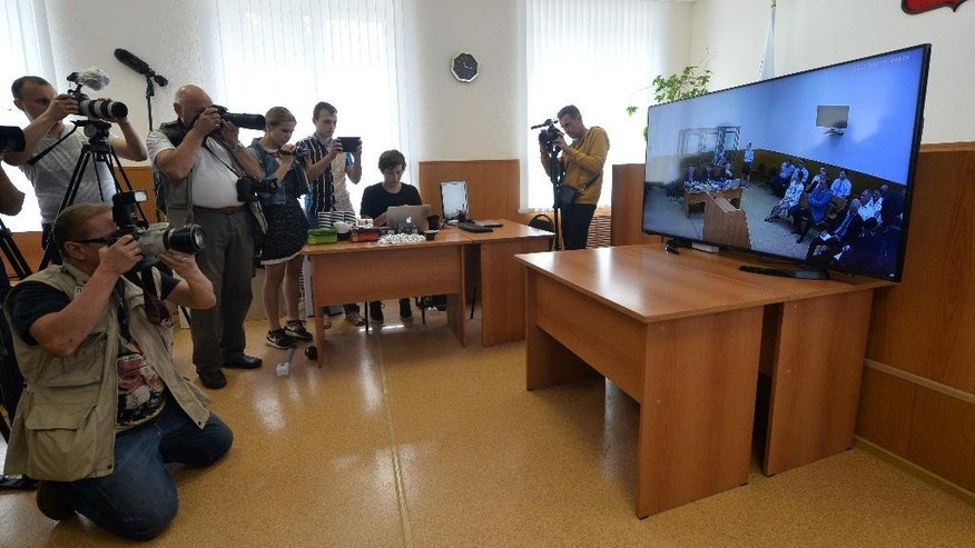 Journalists take pictures from the screen of the TV set broadcasting live from a court room where Nadezhda Savchenko sits in a cage, in the town of Donetsk, Rostov-on-Don region, Russia on Tuesday, Sept. 22, 2015. A Russian court has begun hearing the high-profile case against Ukrainian officer Nadezhda Savchenko, who is charged in the deaths of two Russian journalists in eastern Ukraine. Russian investigators allege that Savchenko, who served in a volunteer battalion fighting with government troops against Russia-backed rebels, provided the coordinates for a mortar attack that killed the journalists in June 2014. (AP Photo)