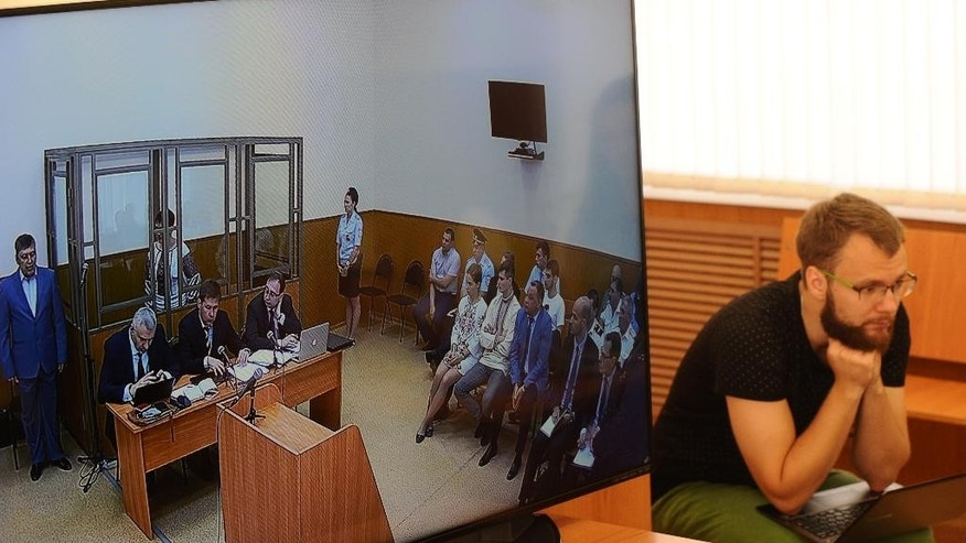 A journalist listens to a live broadcasting from a court room where Nadezhda Savchenko stands in a cage, in the town of Donetsk, Rostov-on-Don region, Russia on Tuesday, Sept. 22, 2015. A Russian court has begun hearing the high-profile case against Ukrainian officer Nadezhda Savchenko, who is charged in the deaths of two Russian journalists in eastern Ukraine. Russian investigators allege that Savchenko, who served in a volunteer battalion fighting with government troops against Russia-backed rebels, provided the coordinates for a mortar attack that killed the journalists in June 2014. (AP Photo)
