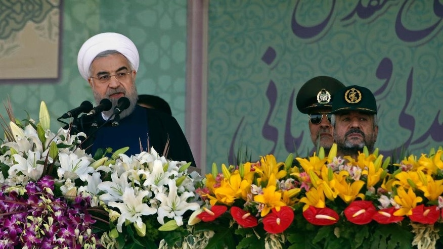 "Iranian President Hassan Rouhani, left, speaks at a military parade marking the 35th anniversary of Iraq's 1980 invasion of Iran, attended by Revolutionary Guard commander Mohammad Ali Jafari, right,in front of the shrine of the late revolutionary founder, Ayatollah Khomeini, just outside Tehran, Iran, Tuesday, Sept. 22, 2015. President Rouhani said Tuesday his country's military is the most reliable force to take on ""terrorists in the region"" - a reference to the extremist Islamic State group. (AP Photo/Vahid Salemi)"
