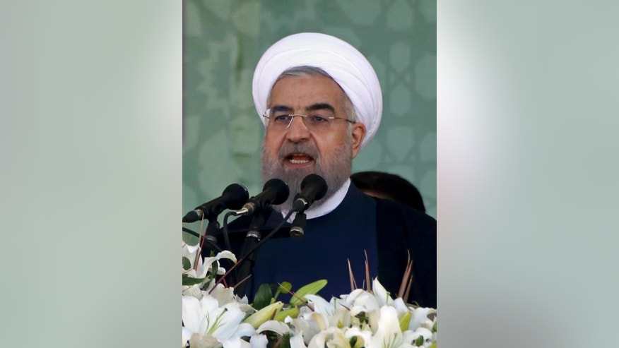 """Iranian President Hassan Rouhani speaks at a military parade marking the 35th anniversary of Iraq's 1980 invasion of Iran, in front of the shrine of late revolutionary founder Ayatollah Khomeini, just outside Tehran, Iran, Tuesday, Sept. 22, 2015. President Rouhani said Tuesday his country's military is the most reliable force to take on """"terrorists in the region"""" - a reference to the extremist Islamic State group while offering help to neighboring nations in case of fight against terrorism. (AP Photo/Vahid Salemi)"""