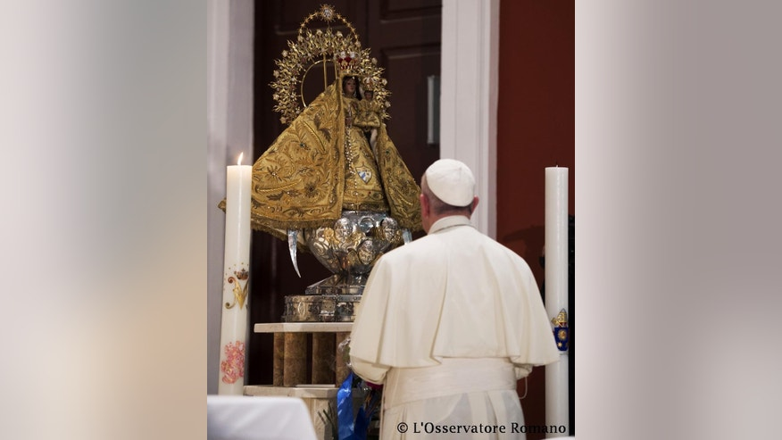 In this photo taken on Monday, Sept. 21, 2015, Pope Francis prays inside the sanctuary of the Virgin of Charity of Cobre, in El Cobre, Cuba. Francis arrived in the sanctuary shortly after landing in the nearby eastern city of Santiago, his final stop in Cuba before heading to the U.S. (L'Osservatore Romano/Pool Photo via AP)