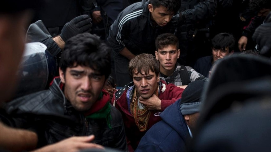 Croatian police officers control a crowd in front of a reception center in Opatovac, Croatia, Tuesday, Sept. 22, 2015. Scuffles have broken out between Croatian police and asylum-seekers after they were barred from entering a newly opened reception center meant to register those seeking sanctuary in Europe. (AP Photo/Marko Drobnjakovic)
