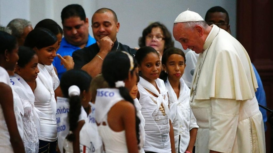 Pope Francis visits with a group of children at the sanctuary of the Virgin of Charity, in El Cobre, Cuba, Tuesday, Sept. 22, 2015. Francis wrapped up a four-day Cuba trip Tuesday and flew north to the United States. (Tony Gentile/Pool via AP)