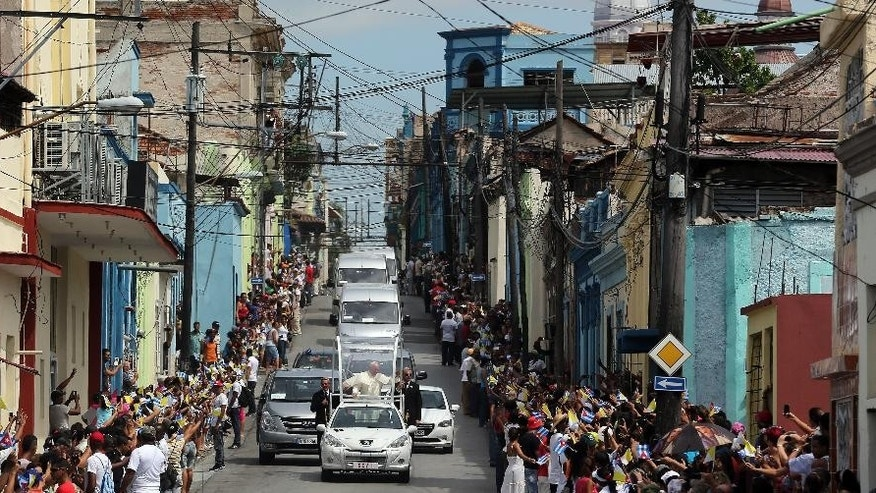 "Pope Francis waves from his popemobile as he makes his way to the airport in Santiago de Cuba, Cuba, Tuesday, Sept. 22, 2015. Francis left Cuba on Tuesday for his first trip to the U.S., wrapping up a four-day visit to the Caribbean island with an appeal to the people to rediscover their Catholic heritage and live a ""revolution of tenderness."" (Alejandro Ernesto, Pool via AP)"