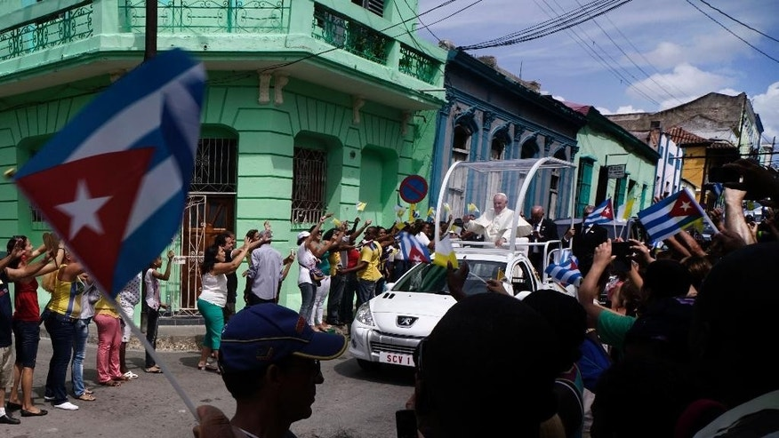"People wave to Pope Francis as he makes his way to the Metropolitan Cathedral in Santiago de Cuba, Cuba, Tuesday, Sept. 22, 2015. Pope Francis on Tuesday called on Cubans to rediscover their Catholic heritage and live a ""revolution of tenderness,"" powerful words in a country whose 1959 revolution installed an atheist, communist government that sought to replace the church as the guiding force in people's lives. (AP Photo/Ramon Espinosa)"