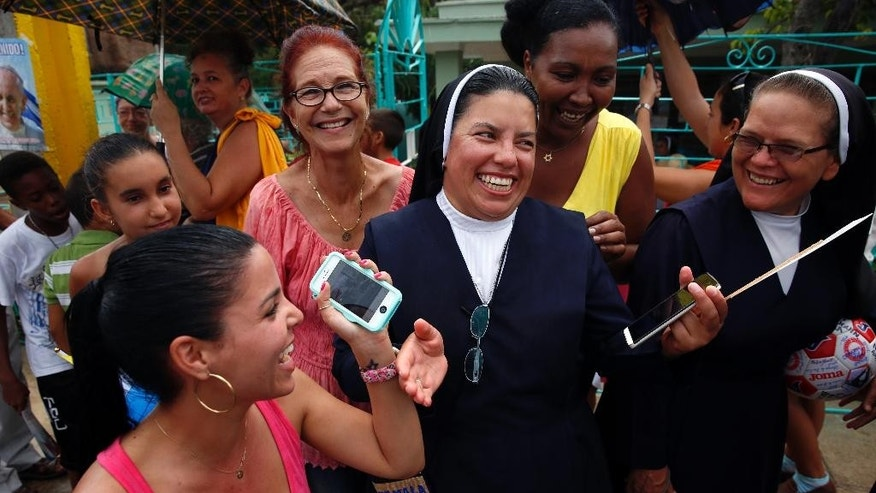 Yulieisis Medreno, 24, smiles after checking the picture she took of Pope Francis riding past on his popemobile to the pilgrimage site Hill of the Cross in Holguin, Cuba, Monday, Sept. 21, 2015. Francis ended his time in Holguin by blessing Cuba's fourth-largest city from the Hill of the Cross, a pilgrimage site overlooking the city. (AP Photo/Enric Marti)