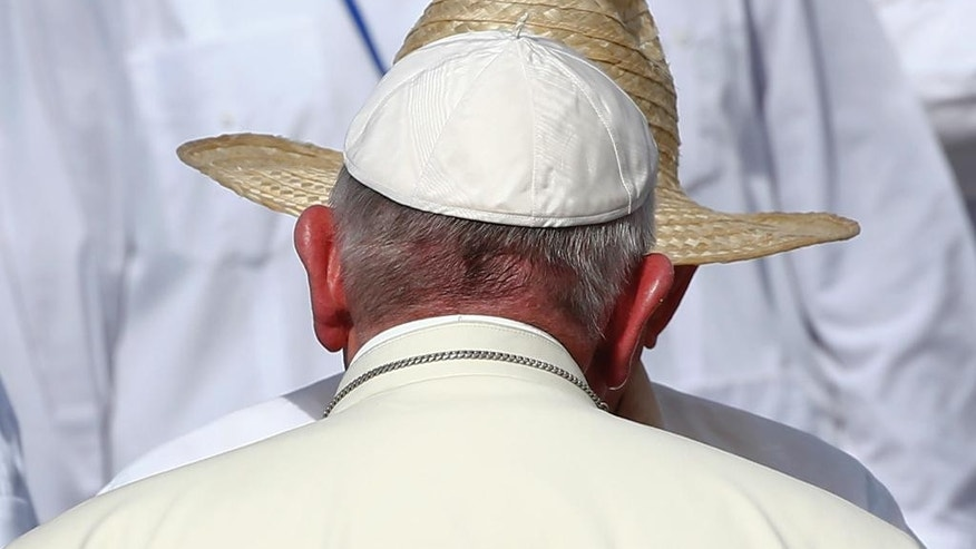 Pope Francis is greeted by Cuba's President Raul Castro as he arrives to celebrate Mass in the Plaza of the Revolution, in Holguin, Cuba, Monday, Sept. 21, 2015. Francis traveled to Cuba's fourth-largest city, Holguin, and celebrated a Mass where Cuban rhythms mixed with church hymns under a scorching tropical sun. (Tony Gentile/Pool via AP)
