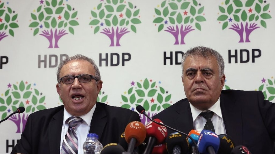 Turkey's Minister for EU Affairs Ali Haydar Konca, left, and Development Minister Muslum Dogan,  members of the of the pro-Kurdish People's Democracy Party, or HDP  speak to the media n Ankara, Turkey, Tuesday, Sept. 22,  2015. The two lawmakers from Turkey's pro-Kurdish party have resigned from the interim government amid continued fighting between Kurdish rebels and government forces in the country's southeast. A statement from the prime minister's office said Tuesday that Konca and Dogan had resigned but gave no reason for their decisions.(AP Photo/Burhan Ozbilici)
