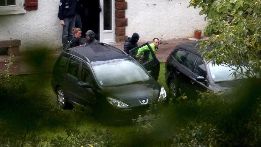 ETA member, David Pla, center right, is escorted by a hooded police officer while his lawyer, Xantiana Cachenaut, center left, looks on, after Pla, was arrested in a joint operation by French and Spanish police in Saint-Etienne-de-Baigorry in France, a few kilometers (miles) from the Spanish border, Tuesday, Sept. 22, 2015. Spain's Interior Ministry said Tuesday that police have dealt a strong blow to the armed Basque separatist group ETA by arresting its top two leaders, David Pla and Iratxe Sorzabal, in an operation in the Pyrenees mountains region of France. (AP Photo/Bod Edme)