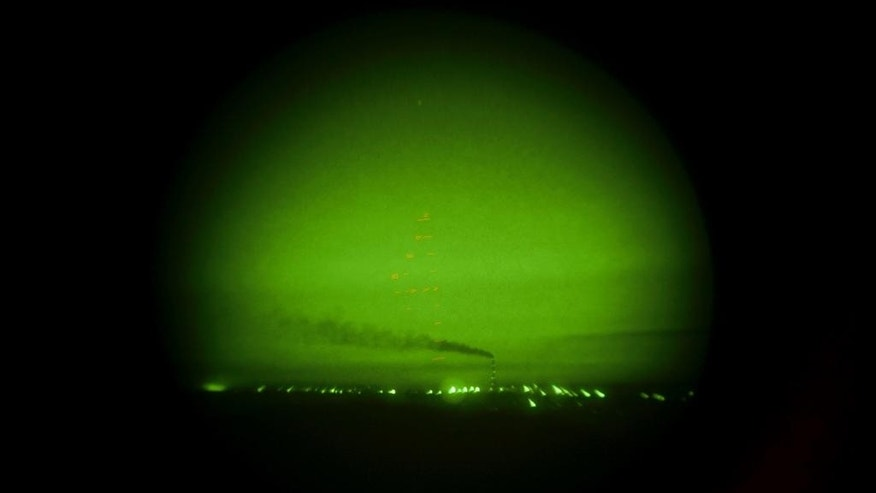 In this Sunday, Aug. 2, 2015 photo smoke, seen through a night vision device, rises from a power plant in the area controlled by Ukrainian government forces near Donetsk in eastern Ukraine. Ukraine's richest man Rinat Akhmetov has been able to straddle the front line in eastern Ukraine, keeping the lights on and people clothed and fed in the rebel-held areas while powering Ukraine's economy and pouring hundreds of millions in taxes into government coffers. (AP Photo/Mstyslav Chernov)