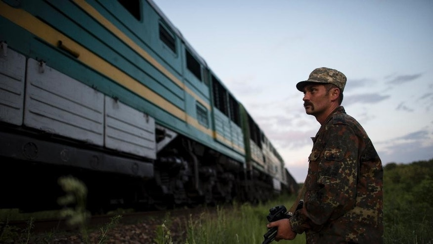 In this Tuesday, June 2, 2015 photo a Ukrainian army officer stands by a train traveling from Ukraine to the rebel-held territory that his platoon had just stopped and forced to go back, in Orekhove, Ukraine. Ukraine's richest man Rinat Akhmetov has been able to straddle the front line in eastern Ukraine, keeping the lights on and people clothed and fed in the rebel-held areas while powering Ukraine's economy and pouring hundreds of millions in taxes into government coffers. (AP Photo/Evgeniy Maloletka)