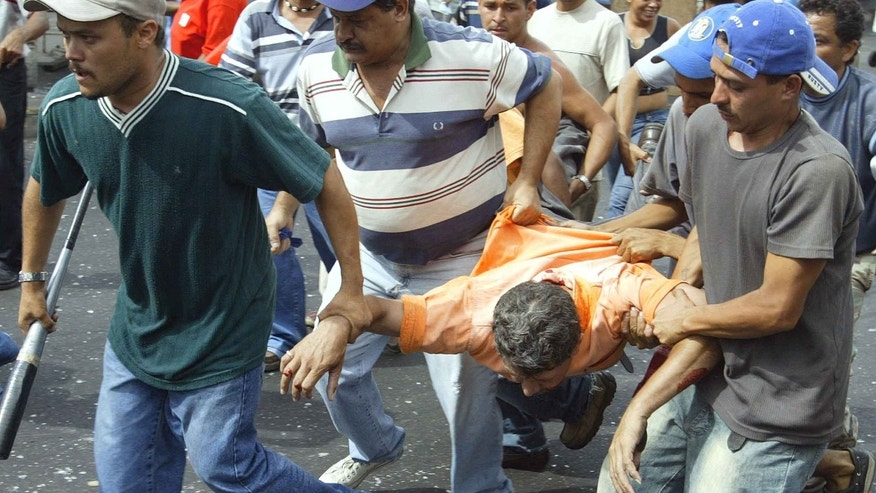 Supporters of Venezuelan President Hugo Chavez carry an injured man June 13, 2003 in Caracas, Venezuela.