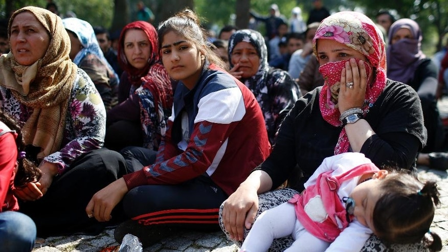 Migrants and refugees listen to an Arabic speaker talk to them about their future as they rest in a stadium used for traditional Kirkpinar Oil Wrestling, while waiting to cross to Europe near Turkey's western border with Greece and Bulgaria, in Edirne, Turkey, Wednesday, Sept. 23, 2015. Hundreds of migrants have made the trek to Edirne in the hope of being allowed to cross into neighboring Greece or Bulgaria and avoid the often-risky journey across the Aegean Sea. Many arrived last week but have been blocked from approaching the border by law enforcement.(AP Photo/Emrah Gurel)