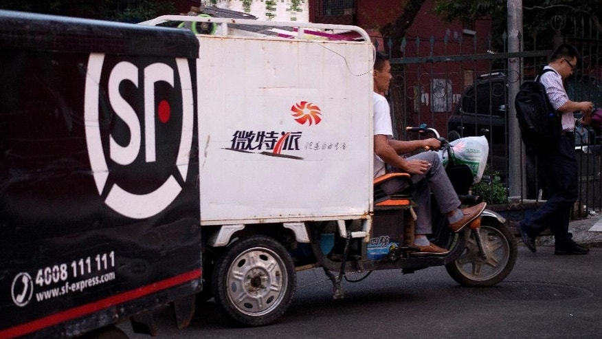 In this Sept. 22, 2015 photo, a delivery company worker rides his cart past a residential building in Beijing.  President Xi Jinping is visiting the United States as leader of a China whose image of economic success has taken a beating. Stock market turmoil and a surprise currency devaluation fueled fears of a Chinese slump with global repercussions. But even a weaker China still is on track to turn in some of the world's strongest growth this year. And some industries including retailing are expanding at double-digit rates. (AP Photo/Andy Wong)