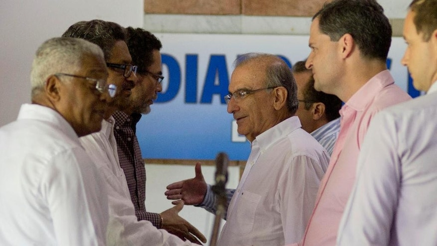 "FILE - In this Dec. 3, 2014 file photo, Humberto de la Calle, head of Colombia's government peace negotiation team, center, talks with Ivan Marquez, chief negotiator for the Revolutionary Armed Forces of Colombia (FARC), after a joint statement in Havana, Cuba. Declaring that ""peace is near,"" Colombia's President Juan Manuel Santos announced a surprise trip Wednesday, Sept. 23, 2015 to Cuba for a key meeting with government negotiators and the rebels' top military commander as he seeks to wrap up talks to end the country's long-running conflict. (AP Photo/Ramon Espinosa, File)"