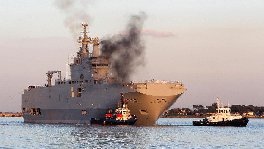 FILE - In this March 5, 2014 file photo, French-built warship BPC Vladivostock, designed to strengthen Russia's ability to deploy troops, tanks and helicopter gunships, leaves the Saint Nazaire's harbor, western France. France says Wednesday Sept.23, 2015 it is selling two Mistral-class warships originally intended for Russia to Egypt instead. Mistral-class warships can carry 16 helicopter gunships, 700 troops and up to 50 armored vehicles. (AP Photo/David Vincent, File)