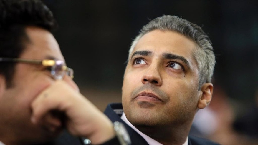 FILE - In this Monday, June 1, 2015 file photo, Canadian Al Jazeera English journalist Mohammed Fahmy, listens to his lawyer, Khaled Abou Bakr during his retrial in a courtroom, of Tora prison, in Cairo, Egypt. Egypt's state-run news agency said Wednesday, Sept. 23, 2015 that President Abdel-Fattah el-Sissi has pardoned 100 people, including Al Jazeera English's Mohamed Fahmy, and prominent human rights activists. (AP Photo/Amr Nabil, File)