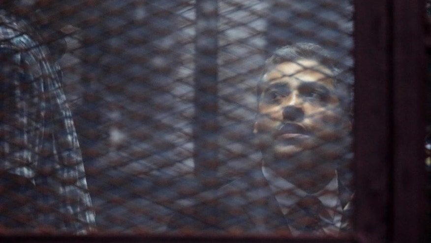 FILE - In this Saturday, Aug. 29, 2015, file photo, Canadian Al Jazeera English journalist Mohammed Fahmy, listens to his verdict in a soundproof glass cage inside a makeshift courtroom in Tora prison in Cairo, Egypt. Egypt's state-run news agency said Wednesday, Sept. 23, 2015 that President Abdel-Fattah el-Sissi has pardoned 100 people, including Al Jazeera English's Mohamed Fahmy, and prominent human rights activists. (AP Photo/Amr Nabil, File)
