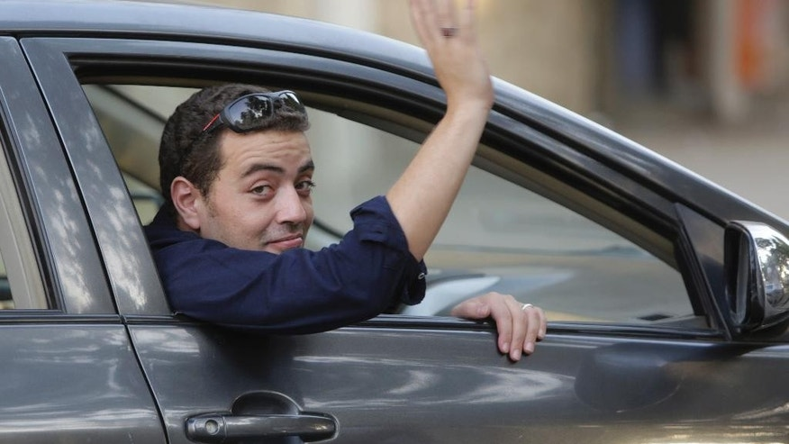 Egyptian Al-Jazeera English journalist Baher Mohammed, celebrates after  being released from Torah prison in Cairo, Egypt, Wednesday, Sept. 23, 2015. Baher and his Canadian colleague Mohamed Fahmy were among a group of 100 people pardoned by Egyptian President Abdel-Fattah el-Sissi on the eve of the major Muslim holiday of Eid al-Adha. The pardon also comes a day before the Egyptian leader is to travel to New York to attend the United Nations General Assembly. (AP Photo/Amr Nabil)