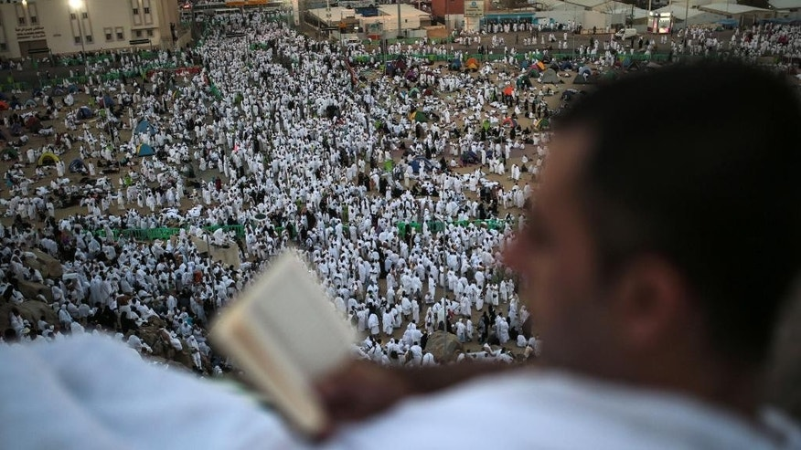 A pilgrim reads the Muslim holy book, the Quran, on a rocky hill called the Mountain of Mercy, on the Plain of Arafat, near the holy city of Mecca, Saudi Arabia, Wednesday, Sept. 23, 2015 during the hajj pilgrimage. Mount Arafat, marked by a white pillar, is where Islam's Prophet Muhammad is believed to have delivered his last sermon to tens of thousands of followers some 1,400 years ago, calling on Muslims to unite. (AP Photo/Mosa'ab Elshamy)