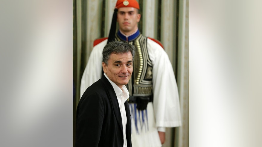 Greece's Finance Minister Euclid Tsakalotos attends new cabinet's swearing in ceremony at the presidential palace in Athens, Wednesday, Sept. 23, 2015. Greece's newly re-elected left-wing government has retained Euclid Tsakalotos as finance minister to continue tough negotiations with other eurozone countries on the terms of a large new bailout deal.(AP Photo/Thanassis Stavrakis)