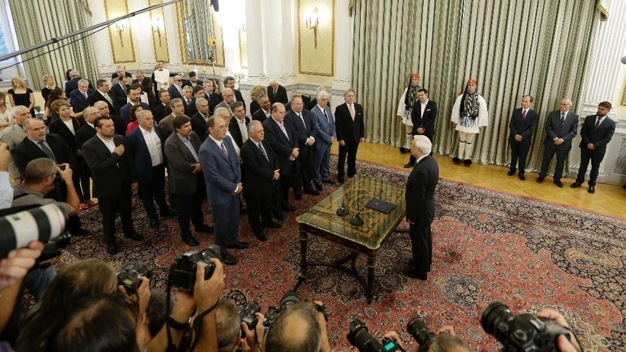 Greece's new cabinet takes a secular oath of office during a swearing in ceremony at the presidential palace in Athens, Wednesday, Sept. 23, 2015. Despite leftwing leader Alexis Tsipras' policy U-turn, he was re-elected by a wide margin in last weekend's general election, and again formed a coalition government with a small right-wing party, the Independent Greeks. (AP Photo/Thanassis Stavrakis)