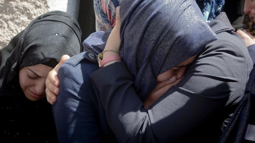 Palestinian women cry during the funeral of Diyaa Talahmeh, 21, in the West Bank village of Khursa, near Hebron, Tuesday, Sept. 22, 2015. Earlier Tuesday, the military said a Palestinian was found dead in a village near Hebron allegedly after an explosive device he was handling went off. The military said it arrived in the area to respond to rock throwing. The Palestinians said the circumstances behind the man's death were unclear.(AP Photo/Majdi Mohammed)
