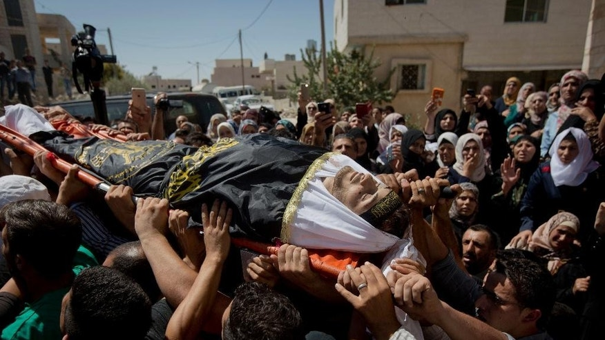 Palestinian mourners carry the body of Diyaa Talahmeh, 21, covered with the flag of the Islamic Jihad militant group, during his funeral in the West Bank village of Khursa, near Hebron, Tuesday, Sept. 22, 2015. Earlier Tuesday, the military said a Palestinian was found dead in a village near Hebron allegedly after an explosive device he was handling went off. The military said it arrived in the area to respond to rock throwing. The Palestinians said the circumstances behind the man's death were unclear.(AP Photo/Majdi Mohammed)