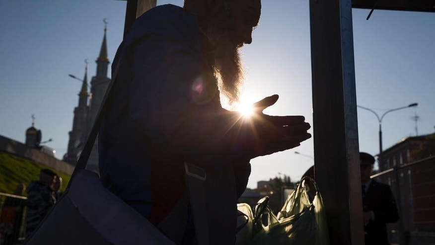 A believer prays as he prepares to go through a security gate to attend the re-opening ceremony of the newly restored Moscow Cathedral Mosque in Moscow, Russia, Wednesday, Sept. 23, 2015. The mosque was demolished and rebuilt to be one of the biggest mosques in the country with a room for 10,000 believers. Russian President Vladimir Putin, Turkey's President Recep Tayyip Erdogan and Palestinian President Mahmoud Abbas will join the re-opening ceremony of the mosque later in the day. (AP Photo/Pavel Golovkin)