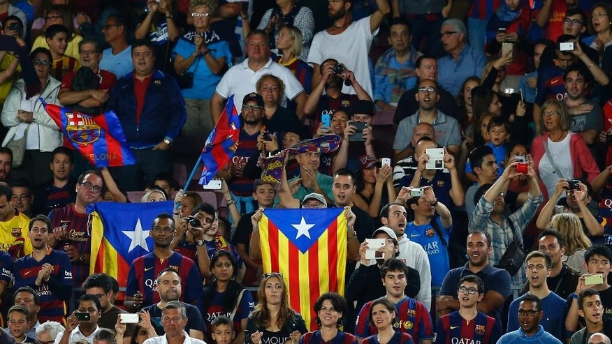 "In this photo taken Sunday, Sept. 20, 2015, FC Barcelona's supporters hold ""estelada"" flags, that symbolise Catalonia's independence, during a Spanish La Liga soccer match between FC Barcelona and Levante at the Camp Nou stadium in Barcelona, Spain. Sports and politics are never far apart in Barcelona's Camp Nou football stadium. Moments after fans emitted a collective sigh last weekend over a narrowly missed strike by Lionel Messi, the chants rang through the stadium as they always do at the 17th minute of a home game: INDEPENDENCIA! INDEPENDENCIA! INDEPENDENCIA! (AP Photo/Manu Fernandez)"