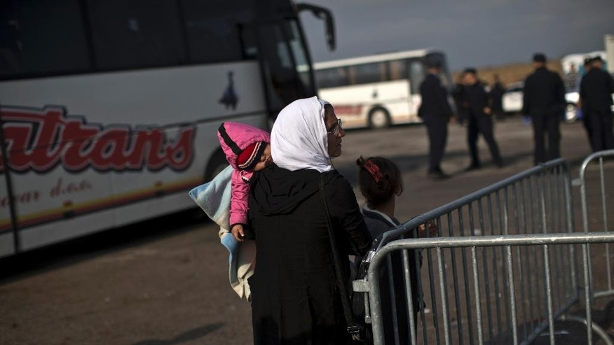 A woman holding a child stands with a girl after arriving by a bus at a registration center for migrants and refugees in Opatovac, Croatia, Thursday, Sept. 24, 2015. Serbia has banned imports of Croatian goods and Croatia has retaliated by barring vehicles with Serbian license plates from entering the country as relations between the two Balkan neighbors deteriorated over the influx of migrants over their border. (AP Photo/Marko Drobnjakovic)
