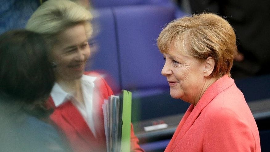 German Chancellor Angela Merkel, right, talks to German Defence Minister Ursula von der Leyen, second left, and German Labor Minister Andrea Nahles, left, as she arrives for a meeting of the German Federal Parliament, Bundestag, at the Reichstag building in Berlin, Germany, Thursday, Sept. 24, 2015. The reflections are caused by windows at the visitors tribune.(AP Photo/Michael Sohn)